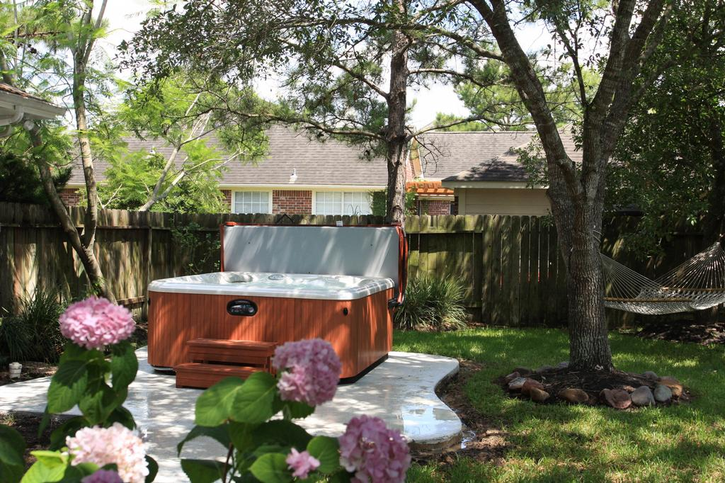 Hot tub With wood and hamock from Richards Total Backyard Solutions in