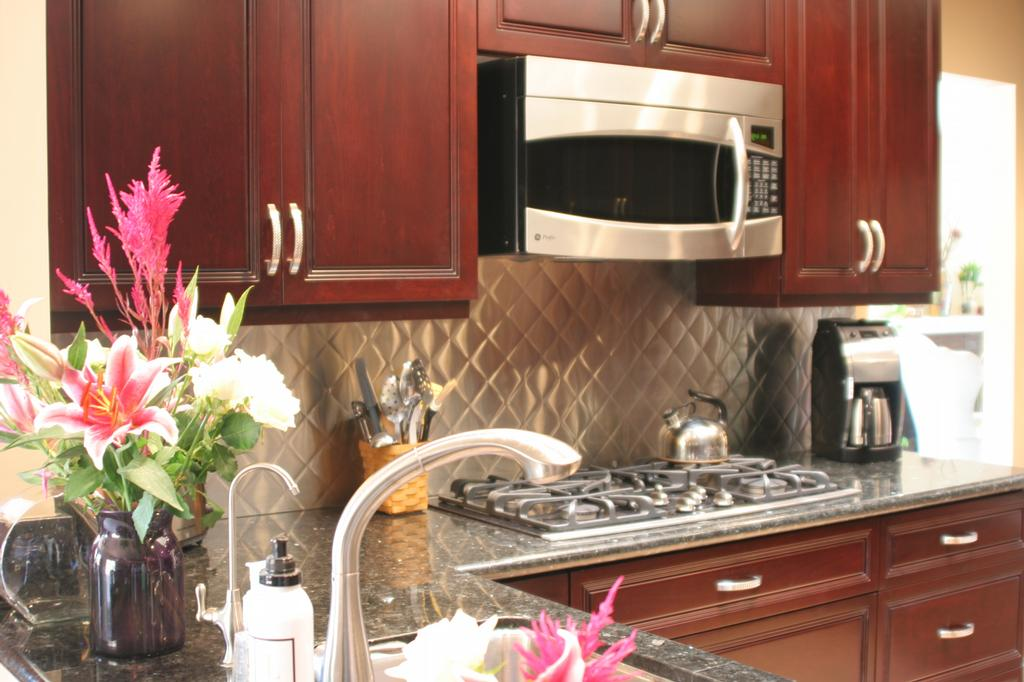 Stainless Steel. With the dark Cherry cabinets, a stone or tile back splash
