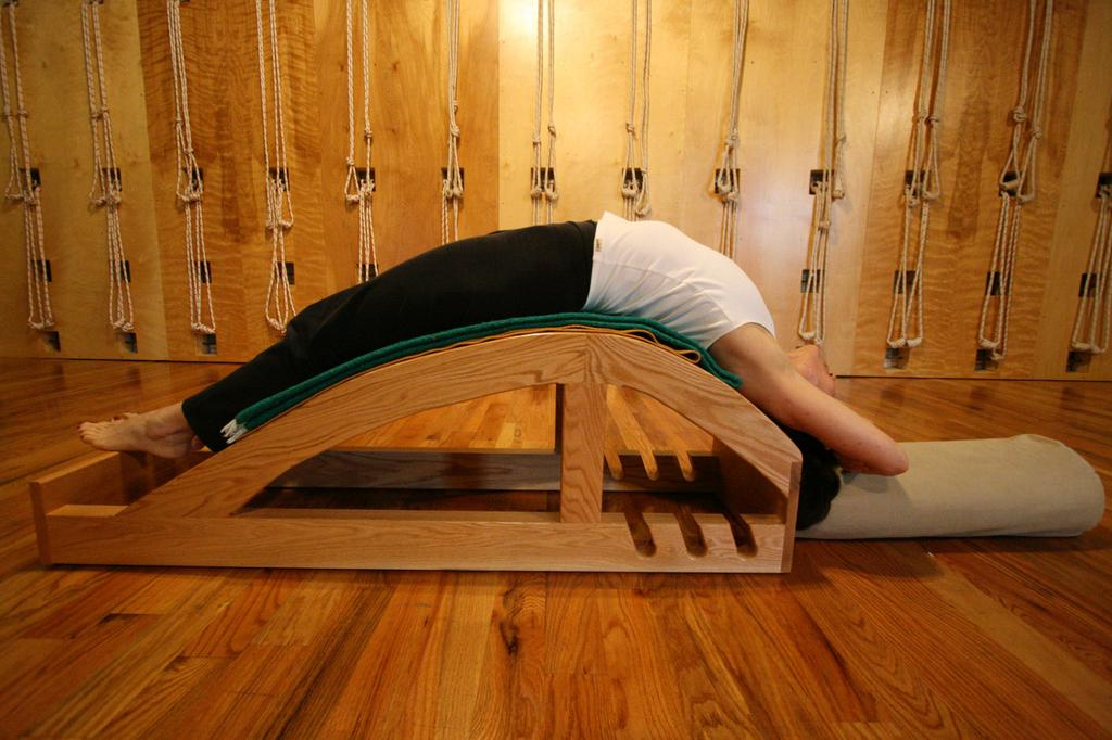 The Viparita Dandasana Bench is one of many props used in the Iyengar method to support the body in order to extend the duration of a pose. by Iyengar Yoga Source