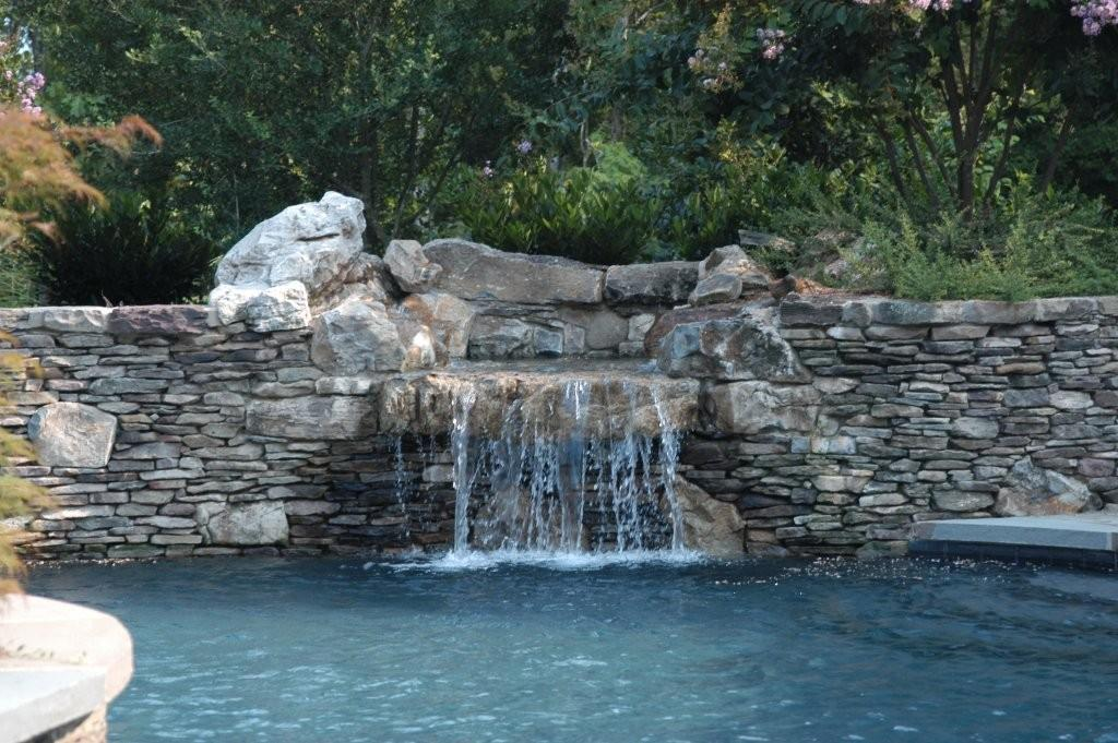 Stone waterfall into swimming pool from stone center of for Stone swimming pool