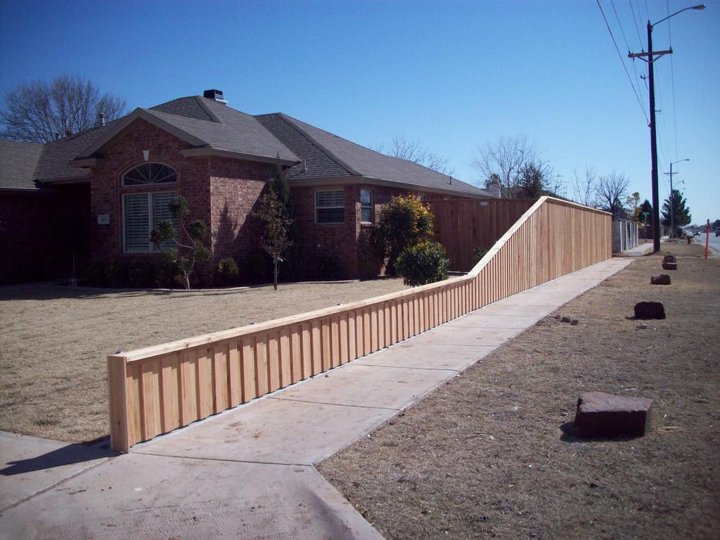 Corner lot fence board on with concrete curb from