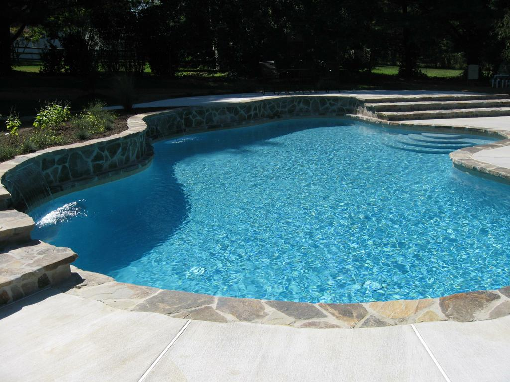 Naturalistic Freeform Swimming Pool With A Raised Beam And Gray Plaster In Jasksonville Maryland